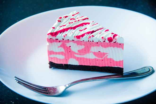 sliced white and pink icing covered cake on white plate with silver colored fork