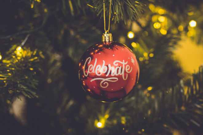 red celebrate print baubles hang on green christmas tree
