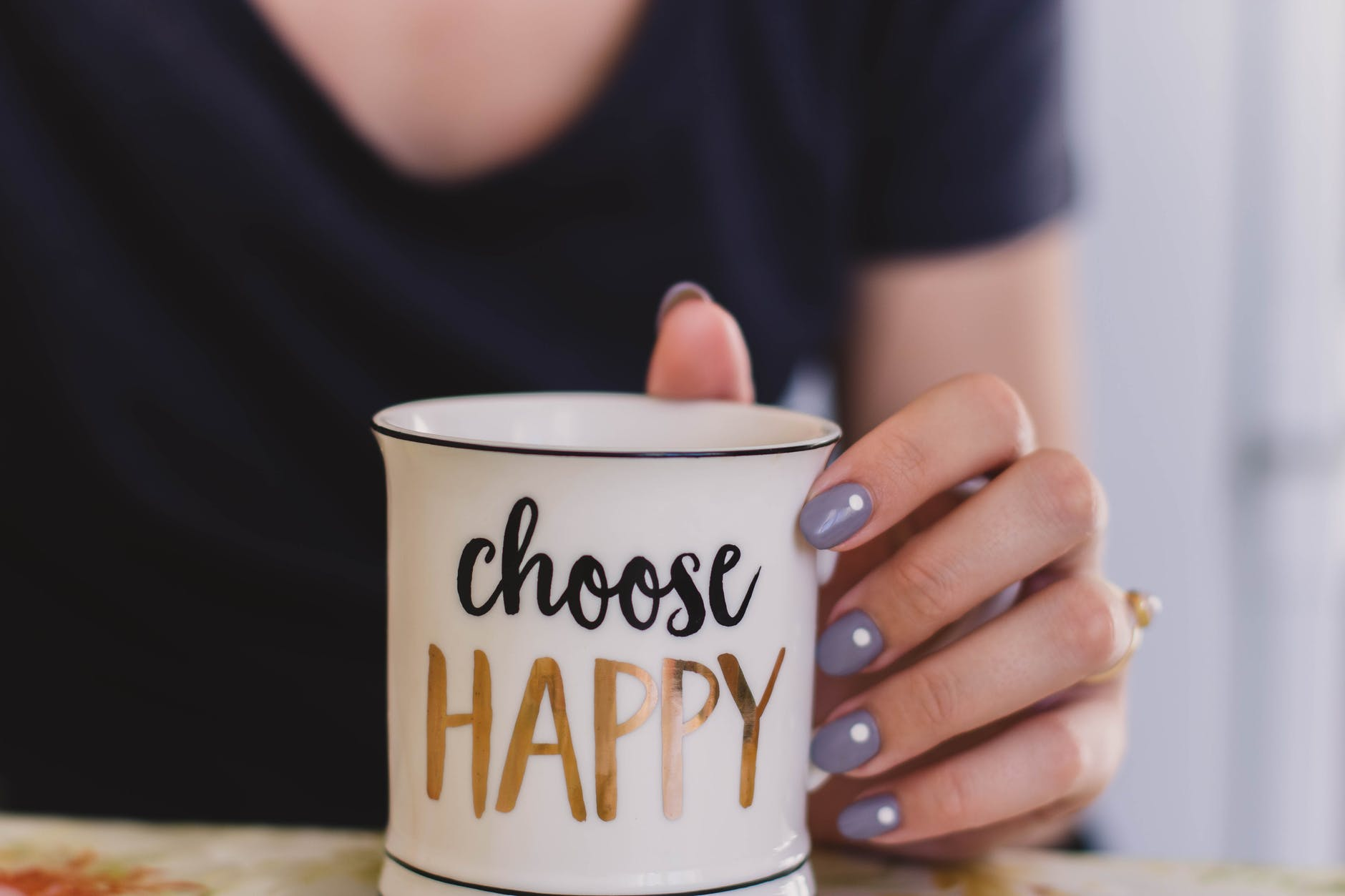 selective focus photography of person touch the white ceramic mug with choose happy graphic